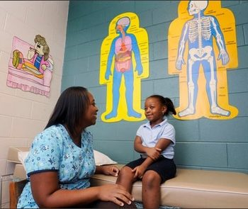 School nurse Tomicka Barnes R.N. talks with kindergarden pupil Tamiyah Dubose at T.S. Morris Elementary School in Montgomery, Ala. on Friday September 18, 2009.(AP Photo/Montgomery Advertiser, Mickey Welsh)